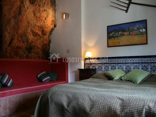 Dormitorio con la pared en piedra