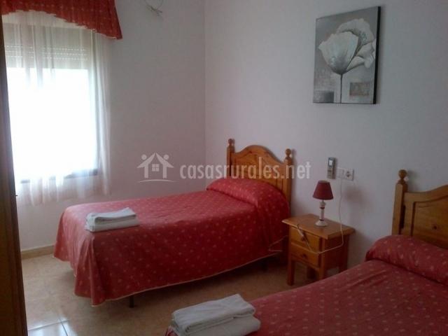 Dormitorio doble con colchas en rojo y mesilla