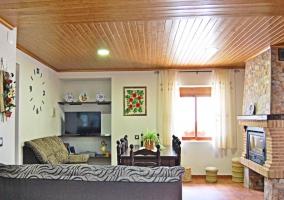Sala de estar con techos de madera y chimenea