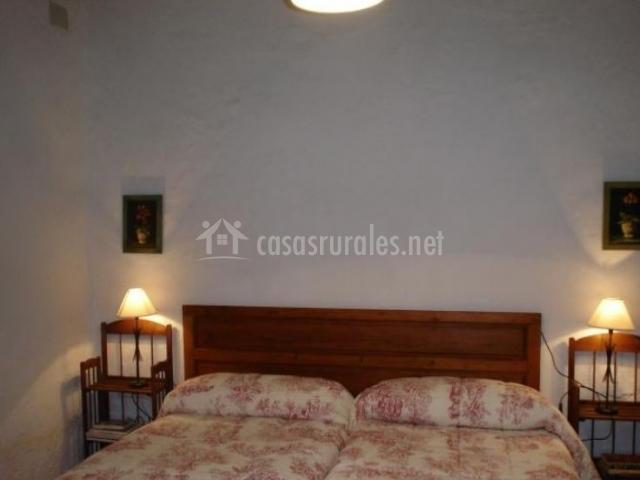 Dormitorio doble con las camas juntas y cabecero de madera