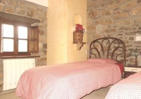 Dormitorio doble con pared en piedra y cabecero