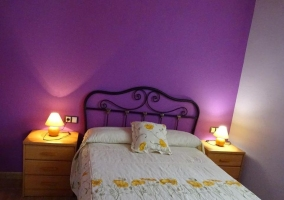 Dormitorio con pared morada