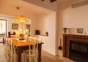 Sala de estar con mesa y chimenea en el frente