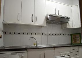 Cocina amueblada en blanco a juego con sus azulejos