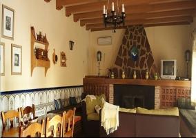Vista completa del salón donde se encuentra la chimenea, los sofás y la mesa de comer