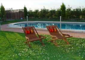 Sillas reclinables junto a la piscina de la casa rural