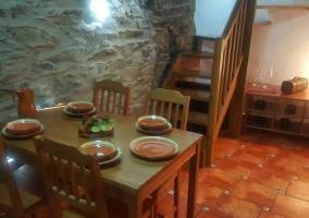 Comedor con la mesa junto a las escaleras