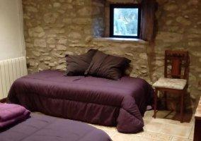 Dormitorio con paredes en piedra