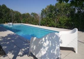 Amplias vistas de la piscina con sillas blancas