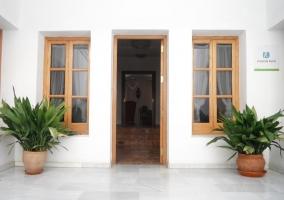 Acceso a la casa con piscina y fachada blanca