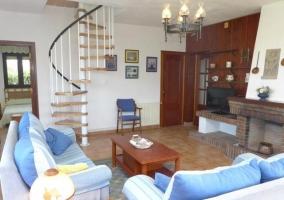 Sala de estar con la chimenea y escaleras