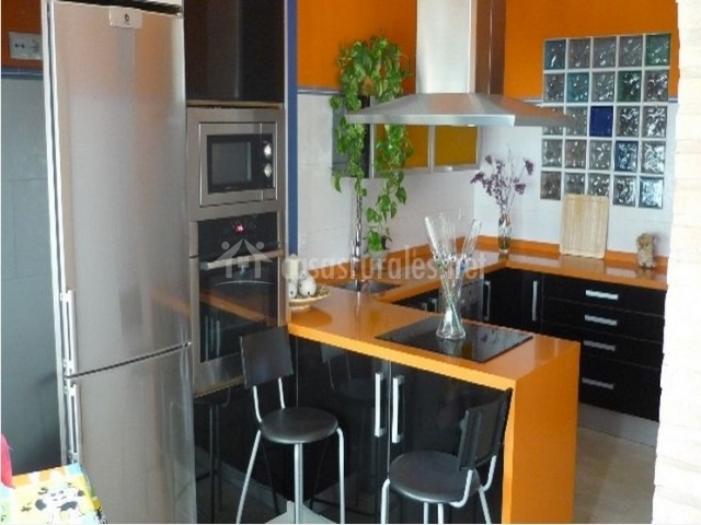 Cocina moderna de la casa rural con toques color naranja