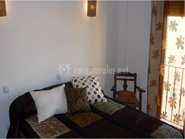 Dormitorio con cama grande y silla junto a la ventana
