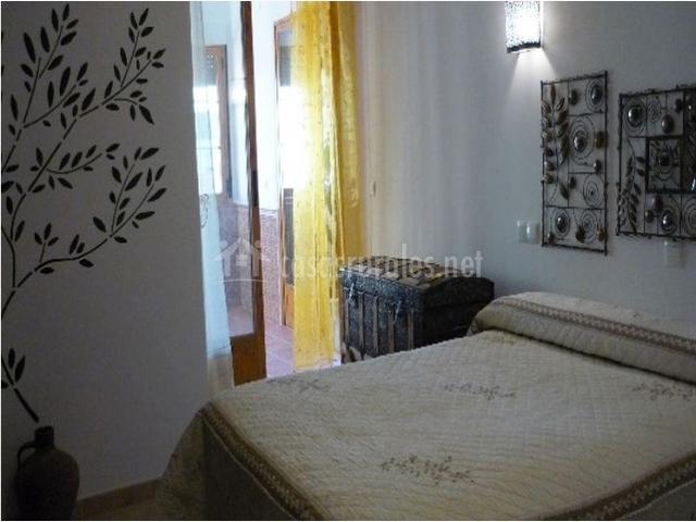Dormitorio con cama matrimonial y baul