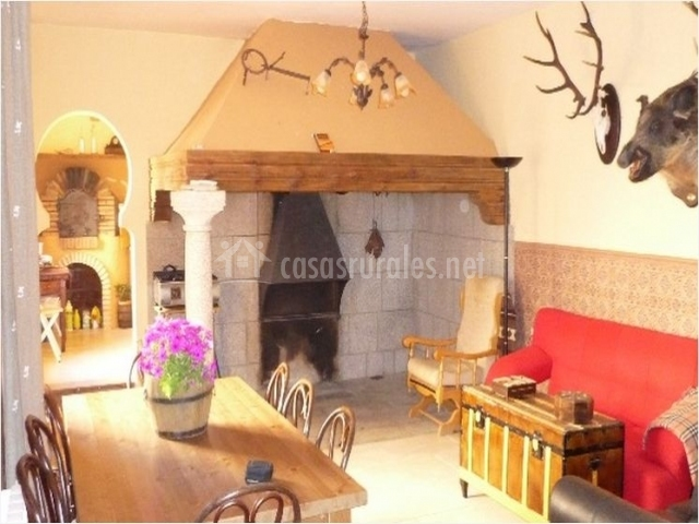 Salón de la casa rural con chimenea y mesa de comedor