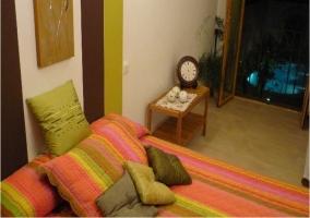 Dormitorio con mesita y ventana con vistas a la piscina