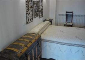 Dormitorio matrimonial con baul y silla