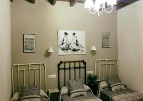 Dormitorio triple con mesillas entre las camas
