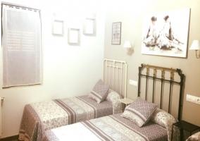 Dormitorio triple con muebles y cuadros