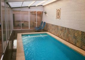 Vistas de la piscina cubierta con hamacas