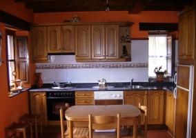 Cocina de la casa con la mesa de comedor en el centro