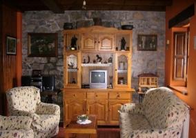 Sala de estar con sillones y mueble de madera en el frente