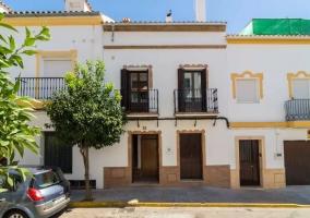 Acceso a la casa con fachada en blanco y amarillo