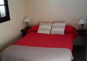 Dormitorio de matrimonio con manta en rojo