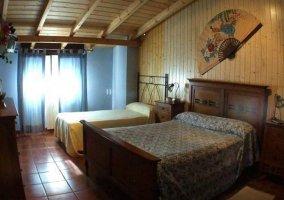 Dormitorio con cama de matrimonio e individual con mesilla