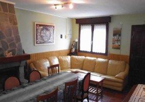 Sala de estar con sillones y chimenea junto a la mesa alargada