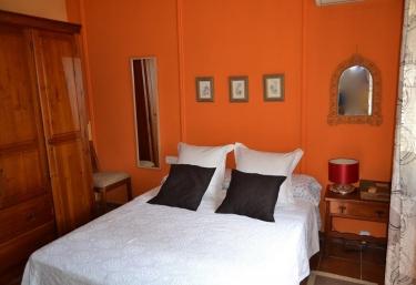 Dormitorio de matrimonio con paredes naranjas