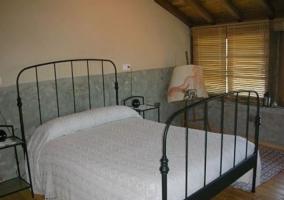 Dormitorio de matrimonio con colchas en color blanco y ventanas