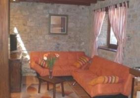 Sala de estar con la mesa de comedor en madera y la chimenea al lado