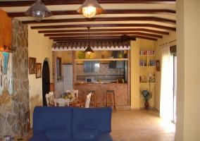 Sala de esrae con la cocina al fondo y su barra con taburetes