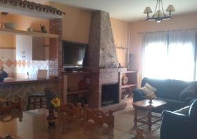 Sala de estar con la mesa de madera y la chimenea