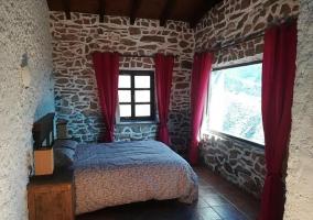 Dormitorio de matrimonio en piedra con ventanal
