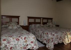 Dormitorio con varias camas individuales y mesilla