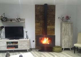Sala de estar con la chimenea encendida y la tele de plasma