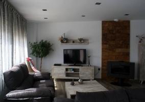 Sala de estar con la tele y la chimenea al lado