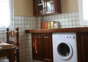 Cocina con lavadora y mesa