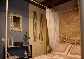 Dormitorio de matrimonio con paredes de piedra y telas