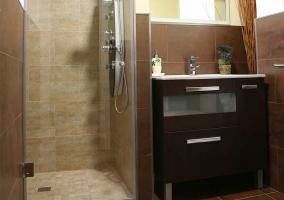 Aseo de la casa con la ducha y los muebles de madera