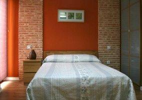 Dormitorio de matrimonio con pared en rojo
