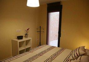 Dormitorio doble con pared y muebles claros
