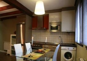 Cocina con mesa de cristal y lavadora