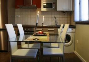 Cocina de la casa con la mesa de cristal delante
