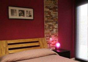 Dormitorio de matrimonio en tonos rojos y cabecero de madera