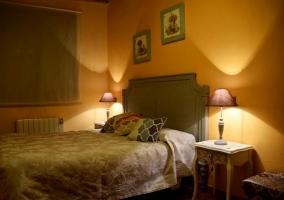 Dormitorio de matrimonio con mesillas de noche y cojines