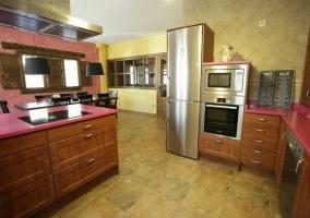 Cocina de la casa con encimera rosa y muebles de madera
