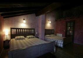 Dormitorio con varias camas y mesillas de noche con luces